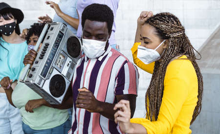 Happy friends listening music with vintage boombox and dancing while wearing face mask outdoor - Multiracial young people having fun during corona virus outbreak - Youth millennial friendship concept Stock fotó