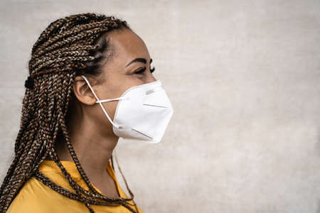 African woman with braids wearing face medical mask - Young girl using facemask for preventing and stop corona virus spread - Healthcare medical and youth millennial people concept