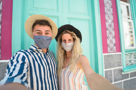 Young couple wearing face mask taking selfie on vacation - People having fun traveling again during corona virus outbreak - Love relationship and tourism concept Stock fotó