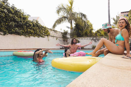 Group happy friends enjoying summer day in swimming pool with inflatable - Young multiracial people having fun in exclusive resort hotel - Youth vacation lifestyle concept