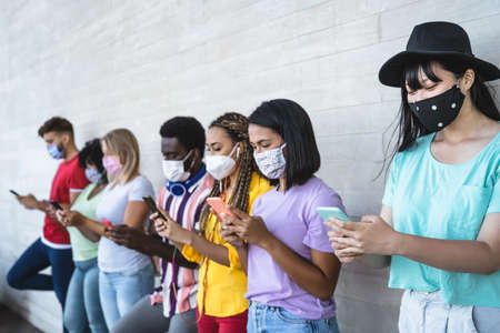 Young people wearing face mask using mobile smartphone outdoor - Multiracial friends having fun with new technology social media app during corona virus outbreak - Youth millennial lifestyle concept Stock fotó
