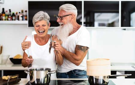 Happy senior couple having fun cooking together at home - Elderly people preparing health lunch in modern kitchen - Retired lifestyle family time and food nutrition concept Stock fotó