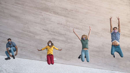Young friends wearing face mask jumping outdoor - Happy people having fun in city after corona virus quarantine - Youth millennial generation friendship and health care concept