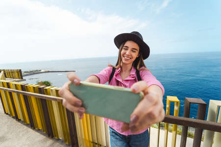 Young woman taking selfie with mobile smartphone during city excursion - Travel influencer having fun with social media in vacation - Millennial people and technology concept Stock fotó