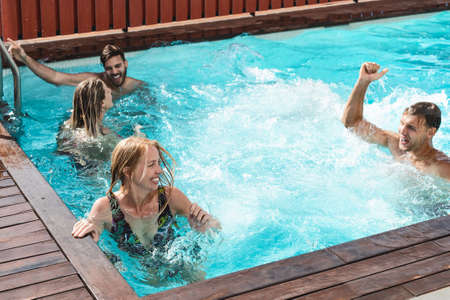 Young people having fun in exclusive pool party - Happy friends enjoying summer holidays in swimming pool - Youth vacation lifestyle concept