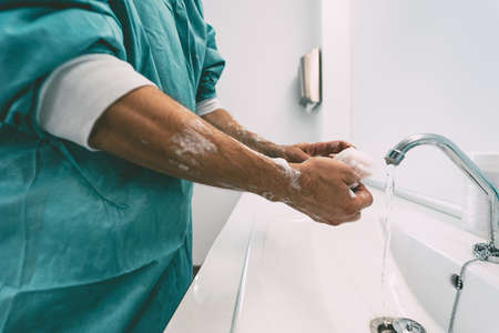 Surgeon washing hands before operating patient in hospital - Medical worker getting ready for fighting against corona virus pandemic - Health care and hygiene concept Stock fotó