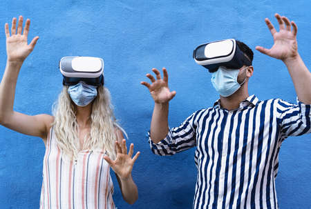 Young couple wearing face surgical mask having fun with virtual reality glasses during outbreak - Millennial people using innovated vr headsets goggles - Youth generation and technology concept