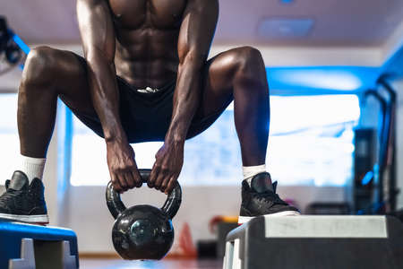 Young African man training inside gym - Fit male doing kettlebell exercise workout session in sport club center - Fitness and bodybuilding lifestyle concept