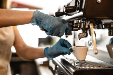 Young woman making coffee espresso while wearing surgical mask and gloves for preventing corona virus spread - Bar owner safety working - Hot beverages and covid-19 rules concept
