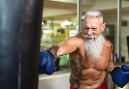 Senior man boxer training hard - Elderly male boxing in sport gym center club - Health fitness and sporty activity concept Stock fotó