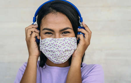 Young woman wearing face mask listening to music with wireless headphones - Latin girl using protective facemask for preventing spread of corona virus - Outbreak health care and technology concept