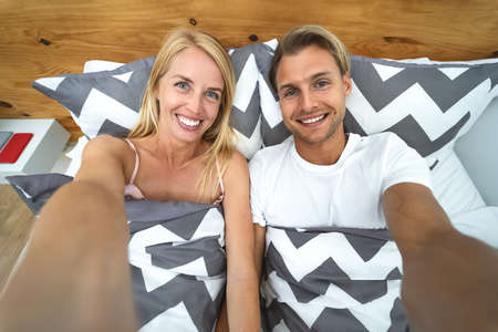 Young couple taking selfie in bed - Happy lovers having fun taking self photos lying on bed below blankets at home - Love relationship and youth culture lifestyle concept Stock fotó