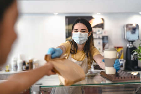 Bar owner working only with take away orders during corona virus outbreak - Young woman worker wearing face surgical mask giving takeout meal to customers - Healthcare and Food drink concept Stock fotó