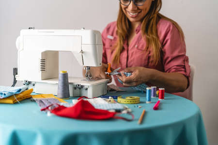 Woman working with sewing machine doing homemade medical face mask for preventing and stop corona virus spreading - Textile seamstress and healthcare people concept
