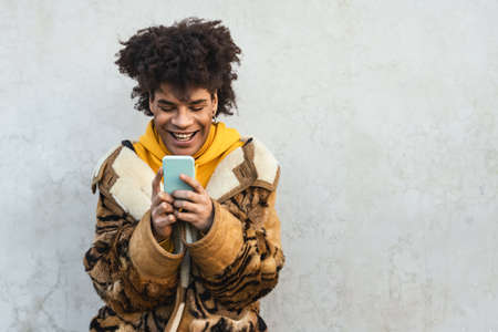 Happy Afro man using mobile smartphone outdoor - Young guy having fun with new technology app for smart device - Youth millennial generation lifestyle and tech concept