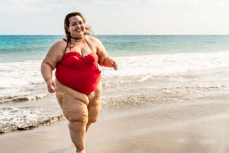 Happy plus size woman running on the beach - Curvy overweight model having fun during vacation in tropical destination - Over size confident person concept
