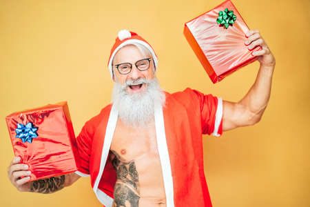 Happy Santa Claus holding Christmas presents - Trendy bearded hipster senior having fun wearing xmas clothes - Elderly people celebrating holidays lifestyle culture