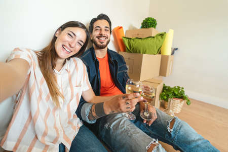 Happy young couple taking selfie while celebrating with champagne in new home first time - Change apartment day and people lifestyle relationship concept Banco de Imagens