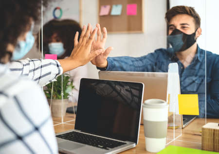 Young people in co-working creative space wearing surgical mask protection and keeping social distance to avoid corona virus spread - Health care and business technology concept Stockfoto
