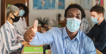 African man thumb up wearing face mask in co-working creative space with team work - Young people working during corona virus pandemic