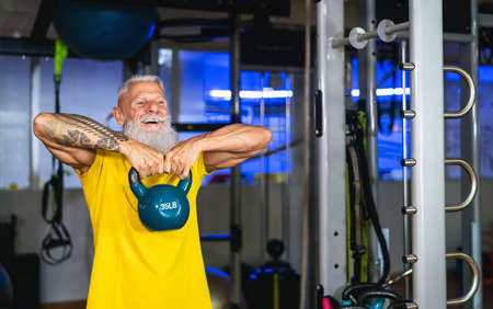 Senior fit man doing kettle bell exercises inside gym - Fit mature male training in wellness club center - Body building and sport healthy lifestyle concept