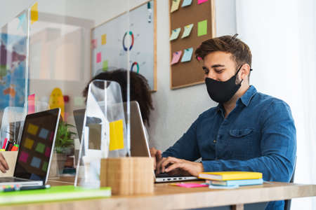 Young people in co-working creative space wearing surgical mask and keeping social distance to avoid corona virus spread - Health care and business technology concept