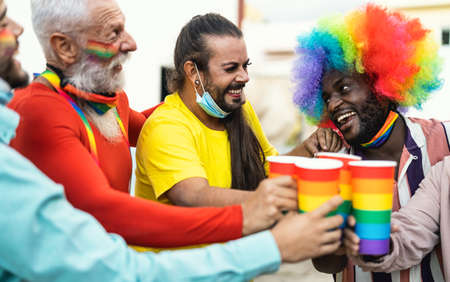 Happy multiracial people cheering and drinking cocktails in pride festival event