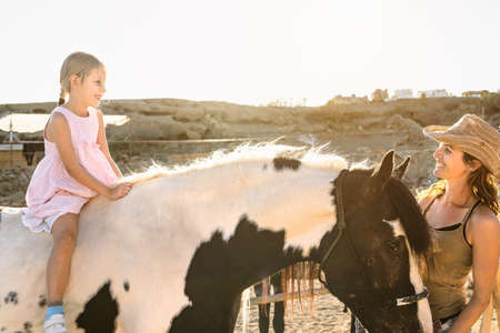 Happy farmer family mother and daughter having fun riding horse inside ranch 写真素材