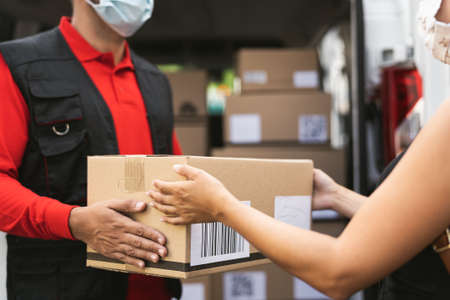 Delivery man wearing face protective mask to avoid corona virus spread - Young woman receiving an online order package from courier express 写真素材