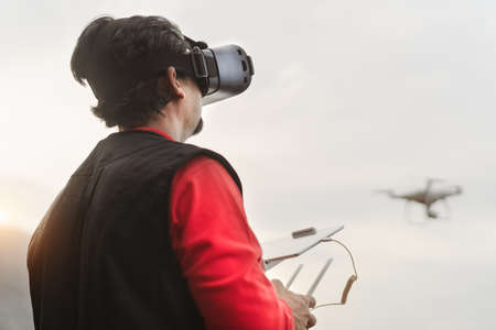 Male professional pilot doing fpv experience using virtual reality glasses and drone - Technology and innovation concept 写真素材