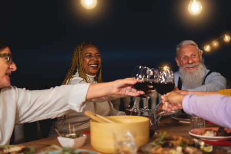 Happy multiracial senior friends toasting with red wine glasses together on house patio dinner - Elderly lifestyle people and food concept 写真素材