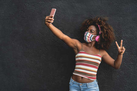 Happy Afro woman taking selfie with mobile smartphone while wearing face colored mask and listening music with wireless headphones