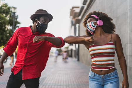 African friends wearing face protective mask while doing new social distance greetings bumping elbows - Youth millennial people and health care guidelines to avoid corona virus spread