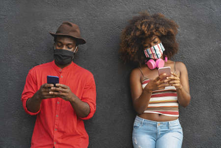 African friends using mobile smartphone during corona virus outbreak - Youth people addiction and technology concept