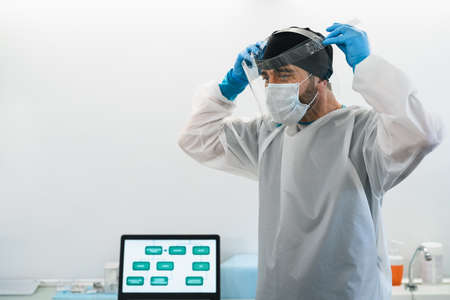 Doctor wearing ppe face surgical mask and visor fighting against corona virus outbreak - Health care and medical workers concept