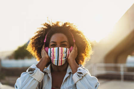 Happy Afro woman listening to playlist music with wireless headphones while wearing face colored mask outdoor