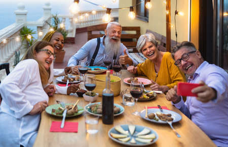 Happy multiracial senior friends having fun dining together while taking selfie with mobile smartphone on house patio - Elderly lifestyle people and food concept 写真素材