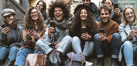 Young people using mobile smartphone outdoor - Millennial friends having fun with new technology social network apps - Youth generation and tech concept