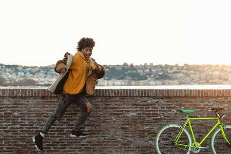 Afro millennial man having fun dancing in the city