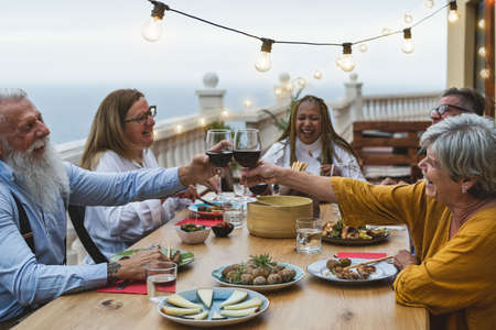 Multiracial senior friends having fun dining together and toasting with red wine on house patio dinner - Food and holidays concept