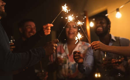 Happy young friends celebrating with sparklers fireworks and drinking cocktails on patio house party - Youth people lifestyle and holidays concept