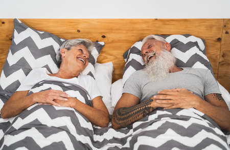 Happy senior couple smiling together in bed - Hipster mature people having funny bed time - Elderly lifestyle and love relationship concept Standard-Bild