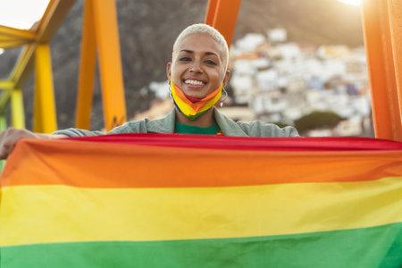 Activist young woman holding rainbow flag symbol of LGBT social movement 写真素材