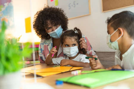 Teacher with children wearing face mask in preschool classroom during virus pandemic - Healthcare and education concept