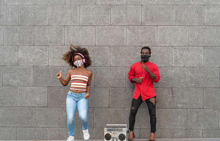 Young African people wearing face mask and dancing outdoor while listening to music with wireless headphones and vintage boombox
