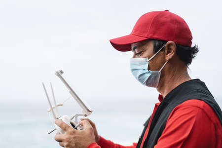 Man piloting drone while wearing face mask to avoid corona virus spreading - Technology and industrial concept 写真素材