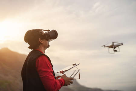 Male professional pilot doing fpv experience with virtual reality glasses and drone - Technology and innovation concept