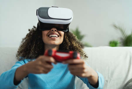 Young African woman playing online video games - Happy gamer having fun on new technology console with virtual reality experience - Youth millennial lifestyle and technology concept