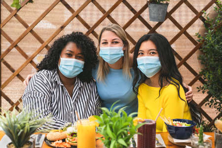 Multiracial friends wearing face mask while having healthy lunch in coffee brunch bar during virus pandemic 写真素材