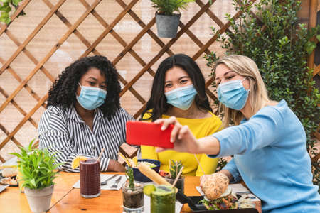 Multiracial friends wearing face mask while taking selfie with mobile smartphone cam in coffee brunch restaurant during corona virus outbreak